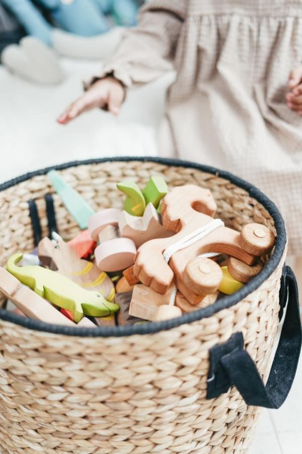 jouets de bebe en bois dans un panier en osier